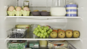 Three refrigerator shelves full of various foods, including grapes, milk and eggs among others.